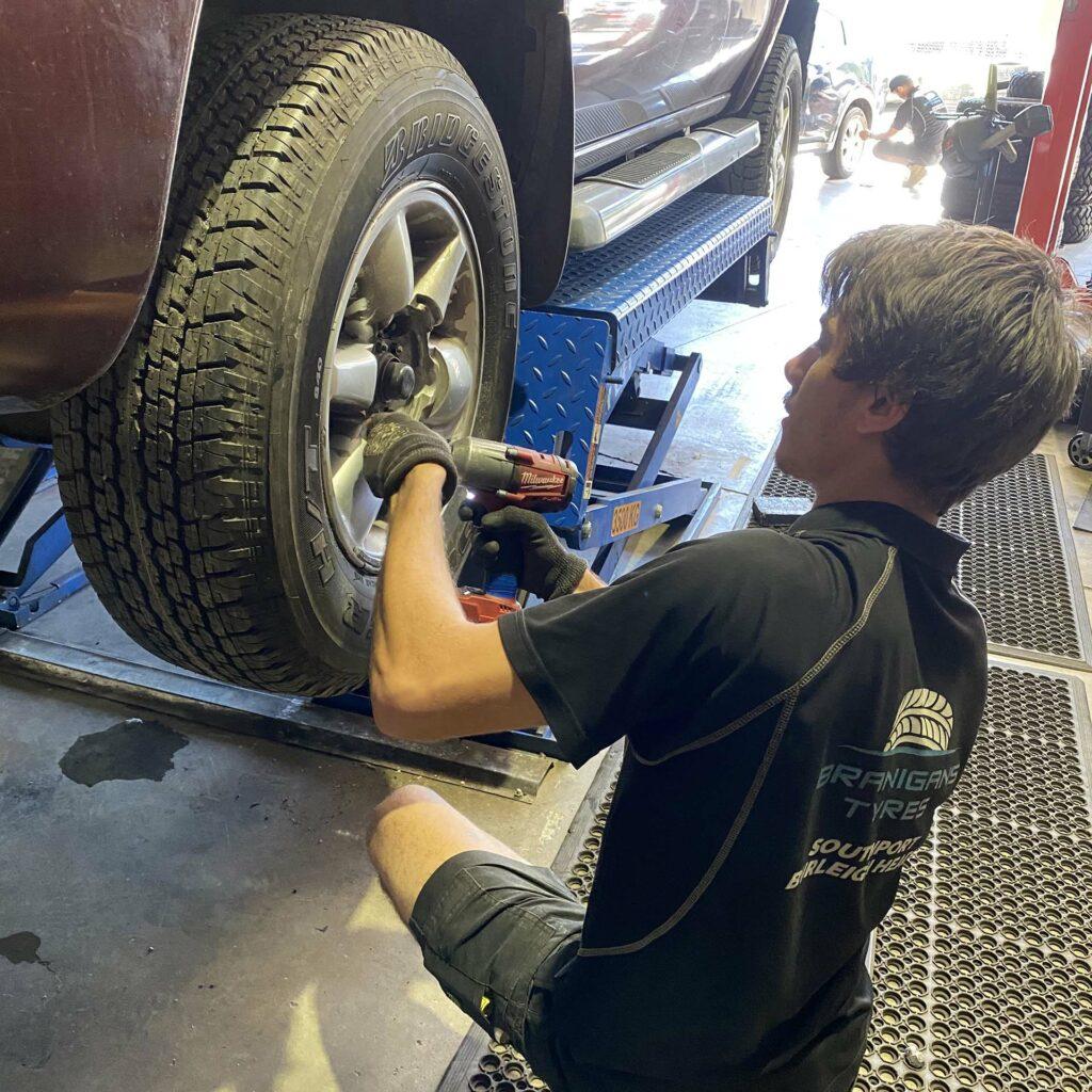 Branigans Burleigh Heads tyre shop team member putting back wheel.